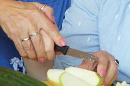 Zwei Personen schneiden zusammen einen Apfel in Spalten.