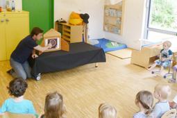Ein Mann kniet vor einem Tisch, auf dem ein Holzkasten steht. In einem Halbkreis um ihn herum sitzen Kinder.