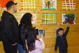 Ein kleiner Junge deutet auf Bilder, die an der Wand hängen. Drei Personen schauen ihm zu.