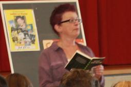Eine Frau mit Brille steht vor einer Tafel und liest aus einem Buch.