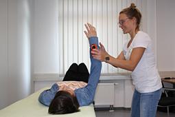 Eine stehende Person hält den Arm einer liegenden Person nach oben.