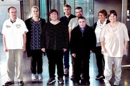 Acht Personen stehen vor einer Glastür und lächeln in die Kamera.