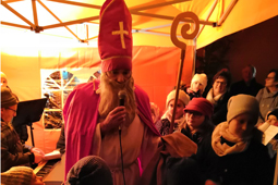 Ein als Bischof Nikolaus verkleideter Mann mit hoher Mütze und Stab steht in einer Menschenmenge und spricht in ein Mikrofon.