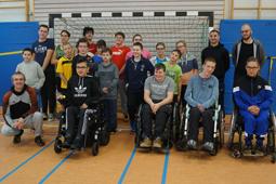 Eine Gruppe Kinder und Jugendlicher sowie einige Erwachsene stehen in einer Sporthalle vor einem Fußballtor.