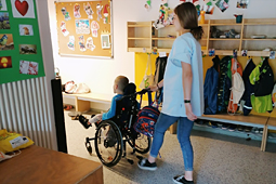 Eine Freiwillige schiebt ein Kind im Rollstuhl durch den Kindergarten, vorbei an einer Garderobe.
