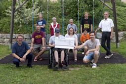 Elf Personen bei der Spendenübergabe auf einem Spielplatz
