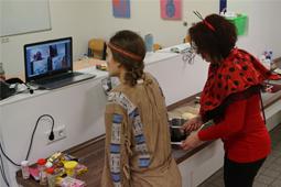 Zwei verkleidete Frauen backen und nehmen an einer Videokonferenz teil.