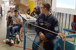 In einer Turnhalle sind mehrere Schüler zu sehen. Ein Junge im Rollstuhl hält ein Plakat hoch.