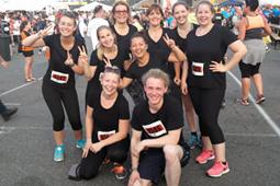 Eine Gruppe aus neun Läufern mit schwarzen T-Shirts strahlt in die Kamera.