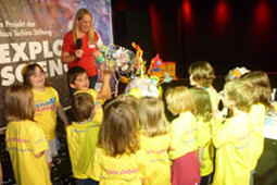 Eine Gruppe Kinder steht an einem Stand und sieht einem Kind zu, das ein gebasteltes Kunstwerk präsentiert.
