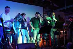 Sechs Personen stehen mit Mikrofonen und Instrumenten auf einer Bühne.