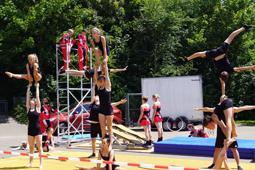 Junge Leute in Turnanzügen zeigen akrobatische Übungen.