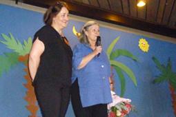 Zwei Frauen stehen auf einer Bühne. Eine hält einen Blumenstrauß in der Hand und spricht in ein Mikrofon.