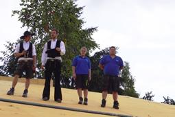 Zwei Zimmerleute und zwei weitere Handwerker stehen auf dem neu erbauten Dach der Kita Stromboli.