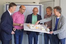 Fünf Männer betrachten das Modell des Kita-Bauprojekts.