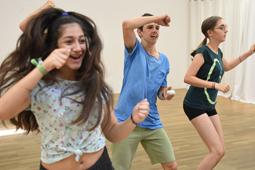 Drei Jugendliche tanzen in einem Trainingsraum.