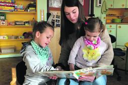 Eine Freiwillige liest Kindern vor.